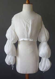 White muslin bodice or chemisette with long sleeves gathered into puffs, c. 1810. A garment like this was typically worn under a short-sleeved or sleeveless dress.