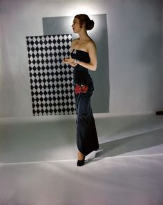 1946 by Horst P Horst    Model is wearing a black satin strapless gown with a rose motif at the hip by Adele Simpson.