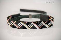 Elegantes Perlenarmband in geometrischen Stil. Es ist handgefertigt aus Glasperlen der japanischen Firma Miyuki und Naturleder. Die Farben des Armbandes: schwarz, weiß, rosa, Gold. () Schiebeverschluss mit hämatitperlen. Die Breite des Armbandes ist 0,47 Zoll (12 mm). Das Produkt wird