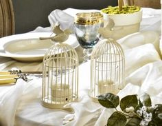Birdcage Tea Light/Place Card Holder #wedding The small door opens to let in the light, setting this vintage bird cage aglow. What a lovely way to add a spark of ambiance to every table! Gift it as a thank-you to your guests, or use it as table decor.http://favorcouture.theaspenshops.com/ivory-birdcage-tealight-holder.html