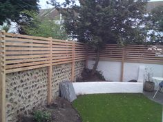 Contemporary Larch Fence to increase height of the existing flint wall in Brighton