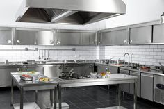 restaurant kitchen Stainless steel utterly defines this large, industrial styled kitchen. With rows of steel cabinetry and work tables, its a high tech look within a black and white tiled space.