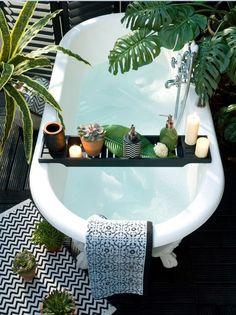 Baignoire îlot blanche au style ancien, pont de baignoire pour garder à portée de main ses produits de beauté et accessoires de bain ! Ambiance tropicale pour salle de bain zen !