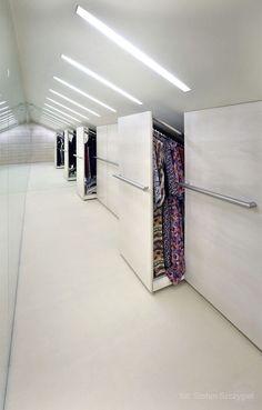 Grand dressing sous pente tout en blanc avec grands spots rectangulaires au plafond et miroir gigantesque. Multitude de rangements avec poignées en inox.