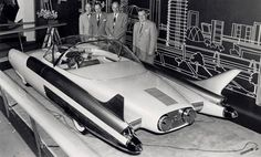 """Appearing at the 1954 Chicago Auto Show, the FX-Atmos featured a glass dome roof, tail fins, rocket exhaust taillights and needle-like radio antennae protruding from front fender pods. The radical cockpit had a center-mounted driver's seat and two-passenger rear seats. Dual handgrips replaced the normal steering wheel and the dash-mounted """"Roadarscope"""" radar screen provided highway information."""