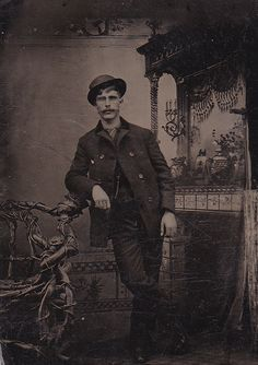 Tintype, what makes this one so great is the decorations and furniture surrounding the man