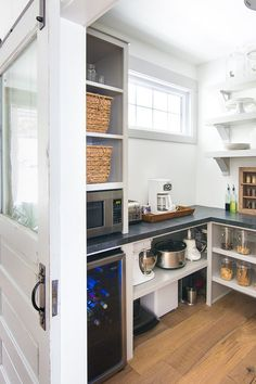Large walk in butlers pantry with grey open shelves and cabinets. Keep all you small appliances hidden, wine fridge, microwave and toaster.