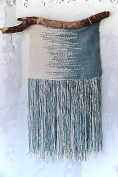 This one of a kind wall hanging in two colors: sea green and cream mounted on a unique piece of driftwood will add a modern boho feel to any space. Materials: wool, cotton, wood Measurement: ca 35cm x 75cm Handmade by Mo