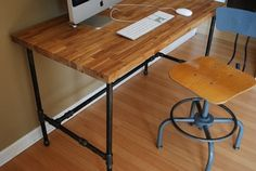 DIY industrial piping desk. This looks like butcher block from IKEA and pipes-- really doable to build.