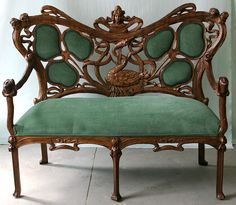 Art Nouveau hand carved wood faux bois and figural upholstered settee, c. 1880, with carved maidens heads, elaborate swan, and shamrocks -- all surrounded by a curving vine frame.