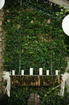Candles are displayed on a hanging shelf adorned with bows, adding a touch of glam to earthy decor.