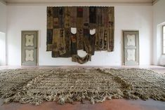 Ibrahim Mahama and his epic art are being exhibited in Italy. Achimota: Aben wo ha, 2014-2015, installation, jute fibres, 1.013 x 515 cm (on the floor, in the foreground); Salifu Kiaw, 2015, installation, coal sacks, 689 x 513 cm (on the wall). Courtesy of the artist and A Palazzo gallery. Photo by BLOOM.