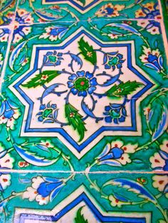 Foliate and star motifs in brilliant blues and greens with a pop of red