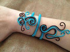 Bracelet en fil aluminium bleu turquoise et marron chocolat. Original avec ses arabesques et ses courbes, ce bracelet en aluminium est très léger à porter et apporte une touche très fantaisie à votre poignet.