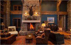 Two seating areas in this extra large greatroom space. Color on the walls, rock walls, and huge soaring fireplace.