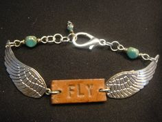 Handmade bracelet with the word FLY surrounded by RockledgeStudios