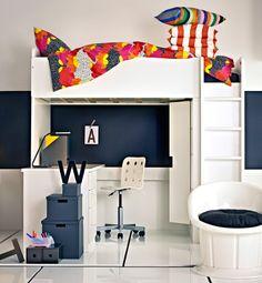 En STUVA loftsäng med skrivbord och förvaring i ett svart och vitt rum med färgglada kuddar och sängkläder i sängen.