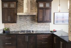 Dark stained cabinetry with glass and stone mosaic backsplash and black granite countertops. #thetileshop