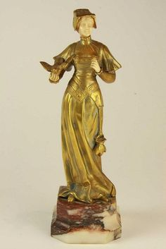A Bronze and Ivory Figure. Omerth, Georges (1895-1925). Circa: 1910. The veiled maiden with long robes with perched dove feeding from her hand. Bronze with ivory face and hands. Signed and numbered 5590. Height: 25cm