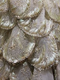 """House of Dior (French, founded 1947), Christian Dior (French, 1905–1957). """"Venus"""" Dress (detail), autumn/winter 1949–50, Haute Couture. Machine–sewn, hand–finished gray silk taffeta and tulle; hand–applique of gray silk tulle and horsehair petals, hand–embroidered with opalescent, gold, and silver gelatin sequins, feather paillettes, synthetic pearls, and clear crystals. Photo © Nicholas Alan Cope. #ManusxMachina #CostumeInstitute"""