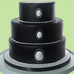 Simple three tier silver and black cake, covered with black rolled fondant. Decorated with silver Cameo's and dots. At the bottom of each tier are tiny silver polka dots, creating a lovely contrast from the classic black. From www.vanillabakeshop.com                ........   #wedding #cake #birthday