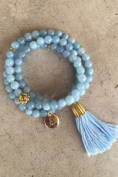 """Our new triple wrap bracelet is handmade of beautiful, baby blue agate beads and finished off with a hand-cut tassel. Strung on elastic cord to comfortably fit most wrists (sized to fit up to approximately a 7 1/2"""" wrist) Triple wrap style Gold-tone lotus flower guru bead Gold-tone buddha charm Gold-tone tassel cap with beautiful, baby blue hand-cut cotton tassel Can also be worn as a necklace Made in our San Francisco, California workshop"""