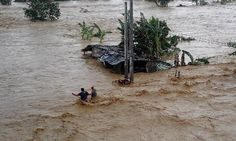 Residents wade through floodwater in Nueva Ecija Philippines