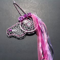 "Lilac Unicorn Dream Catcher 7"" Width X 19"" Length Accented with Lilac glass beads, multi-colored ribbons and purple flowers. Handmade eye with crystal center."