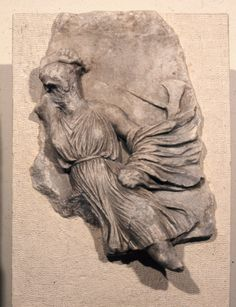 Fragment of the frieze showing the Amazonomachy. An Amazon wears a knee-length dress, girt somewhat above the waist with a rounded belt, and a cloak wound round the left hand and covering the left forearm and elbow, with loose and flying end out to right; her hair is waved back from the forehead but is broken away elsewhere. She is moving to left and her right arm is raised and bent back so that the hand and wrist lie on the head, in the act of striking with an axe, the shaft and head of…