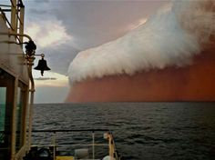 The handout photo taken on January 9, 2013, and posted by Perth Weather Live shows a towering red dust storm over the ocean ahead of the cyclone approaching Onslow on the West Australian coast.  Tug boat worker Brett Martin, who captured the fearsome pictures 25 nautical miles from the town of Onslow, reported conditions were glassy and flat before the storm hit late on January 9.  But when the wild weather arrived, the swell lifted to two metres, winds increased to 40 knots and visibility…