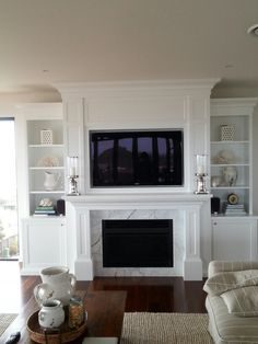 White fireplace with white shelves constructed on each size, and white or ivory furniture. Black TV and  fireplace in contract black and grey wood floors. Hampton Fireplace