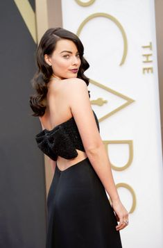 Margot Robbie on the red carpet at 2014 Oscars in strapless black Saint Laurent by Hedi Slimane gown