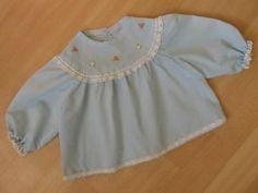 Licht blauw lief babyjurkje met handgeborduurde bloemetjes, maat 62-68. Met kanten sierbandjes, pofmouwtjes en 3 knoopjes aan de achterkant.