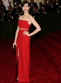 Anne Hathaway - Anne Hathaway se atrevió con el rojo de este vestido efecto crop top con abertura central en la falda de Calvin Klein Collection, zapatos metalizados también en rojo de Gianvito Rossi, clutch negro de Rauwolf y pendientes de Vhernier.