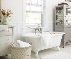 Vintage Vibe - In this refurbished 1920s master bath, a contemporary paint palette of warm white and pale gray makes flea market furnishings shine. The sink, plumbed into a vintage dresser, wraps up style and function in a pretty package, while an old apothecary cabinet holds supplies in period style. Beaded-board wainscoting injects subtle white-on-white pattern around the room, while the large woven towel basket provides interesting texture.