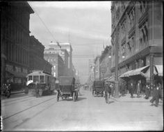 "View of 16th (Sixteenth) Street in Denver, Colorado; shows automobiles, a horse-drawn carriage, bicyclists, pedestrians, an electric street car ""Union Depot - #244"" a clock, Daniels & Fisher tower construction, and signs: ""The Braman Co."" ""A. J. Stark & Co."" and ""A. T. Lewis & Son."""