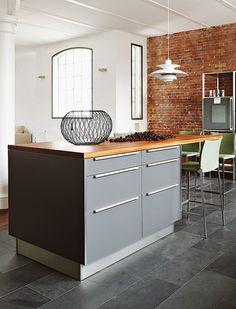 Loft Hamburg. cherry wood benchtop and red brick wall on grey kitchen