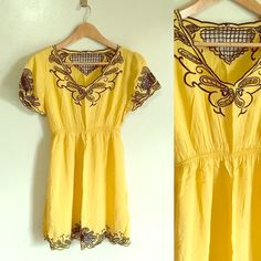 $5Yellow dress top Very pretty dress with black stitching details on collar and bottom hem. It has a light stain its so small you would have a hard time seeing it. It could probably be washed off i just dont have time Dresses Mini