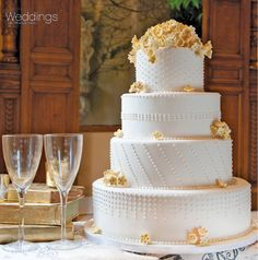 Four tiered white wedding cake with pale orange flowers