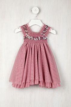 She'll feel like a princess wearing the Rose Colored Paparazzi Dress.  - Square neckline  - Sleeveless  - Back self tie closure  - Smocked bodice  - Sequin and ruffled trim throughout  - Layered tulle skirt