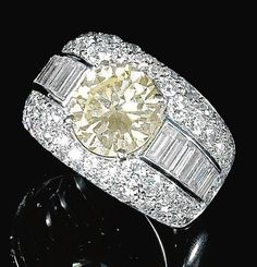 DIAMOND RING, BULGARI, 1960S. Claw-set to the centre with a circular-cut diamond, the mount set with brilliant-cut and baguette diamonds, size 53, Bulgari.