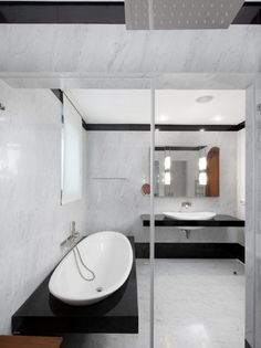 Elad Gonen create modern black and white bathroom features alcove shower with white oval drop in sink on floating black baseboard