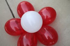 Giant Balloon Flowers - cut a piece of cardboard large enough for 5-6 small slits around the edges and one in the middle, blow up balloons, push one through each slit and secure with tape from behind. Voila! Super easy balloon flowers you can secure to the wall that actually keep their shape!