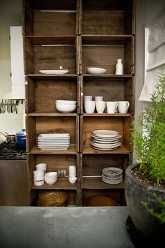 Vintage crates serve as open kitchen cabinets - i've got some apple crates I can use like this - yippee!