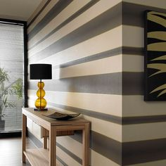 Indulge yourself with the stunning simplicity of a classic bold stripe modern with an irridescent metallic overlay and a contemporary color palette - hang vertically or horizontally for a stylish look. Try this brown and gold wallpaper for a bold look.