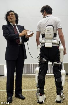 Cyberdyne's CEO Yoshiyuki Sankai, left, presents the medical 'Robot Suit HAL'