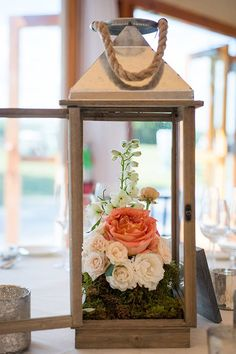 A simple wedding centerpiece made of a wooden lantern filled with roses and peonies | @snapgirls | Brides.com Floral Design : www.greenlionweddings.com