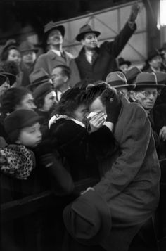 """Henri Cartier Bresson (World War II is coming to an end. A mother and a son reuniting? As they embrace in the crowded port of New York, their faces are barely visible. But we can clearly see expressions of others waiting for their beloved ones: tense, hesitant, impatient, cautiously joyful. """"New York 1946"""" states the caption. Cartier-Bresson felt nothing more elaborate was needed.)"""