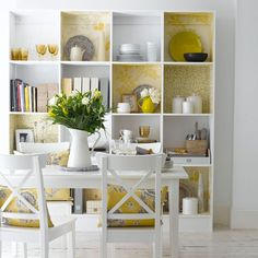 Shelving unit in dining room using yellow accents    Store away everyday essentials or showcase your favorite pieces in this floor-to-ceiling shelving unit. Add a touch of color to the scheme with zesty lemon wallpaper and matching accessories.