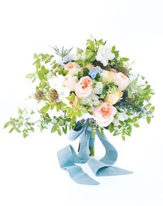 romantic bouquet of white azalea, peach Juliet cabbage roses, blue bells, Queen Anne's lace, blue thistle, scabiosa pods, carmel antique roses, mock orange, and honeysucker by Holly Chapple
